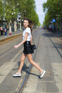 Young woman crossing a street with tramway tracks in the city - GIOF04288