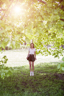 Smiling young woman standing in a park - GIOF04294