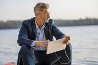 Mature businessman with earphones and tablet relaxing at lake - FMKF05210