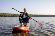 Businessman paddling on lake - FMKF05222