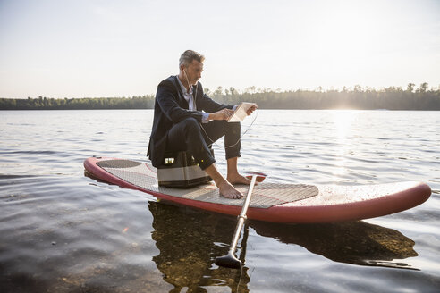 Businessman sitting on paddleboard on a lake using tablet and earphones - FMKF05228