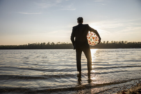 Back view of businessman with beach ball standing at lakeshore watching sunset - FMKF05231