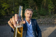 Portrait of mature businessman toasting with beer in nature - FMKF05234
