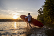 Man with paddleboard walking into lake by sunset - FMKF05237
