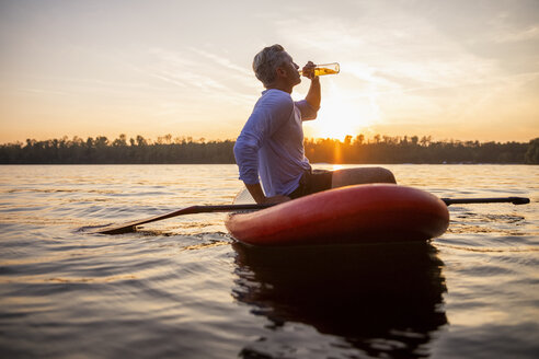Man sitting on paddleboard on a lake by sunset drinking beverage - FMKF05240
