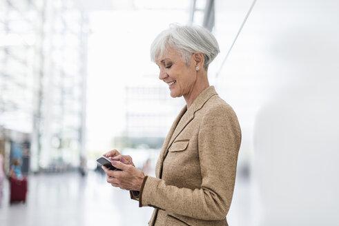 Smiling senior businesswoman using cell phone - DIGF05015