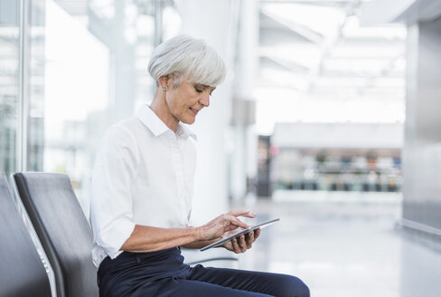 Senior businesswoman sitting in waiting area using tablet - DIGF05018