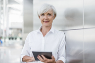 Portrait of smiling senior businesswoman holding tablet - DIGF05021