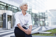 Smiling senior businesswoman sitting outside looking around - DIGF05033