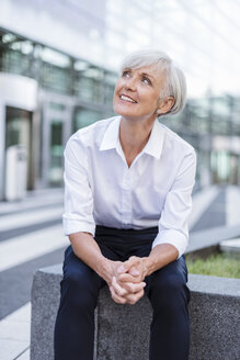 Smiling senior businesswoman sitting outside looking up - DIGF05036