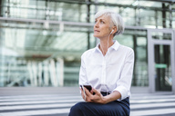 Senior businesswoman sitting outside with smartphone and earbuds - DIGF05039