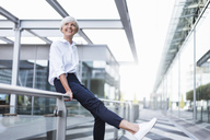 Happy senior woman sitting on railing in the city looking around - DIGF05042