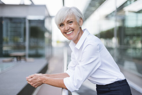 Portrait of happy senior woman leaning on railing in the city - DIGF05045