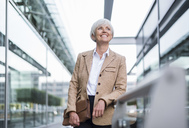 Smiling senior businesswoman leaning on railing in the city looking up - DIGF05051