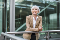 Portrait of smiling senior businesswoman leaning on railing in the city looking up - DIGF05054