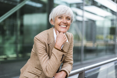 Portrait of smiling senior businesswoman leaning on railing in the city - DIGF05057