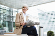 Smiling senior businesswoman sitting in the city with newspaper - DIGF05060