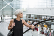 Senior woman on escalator at the airport - DIGF05072