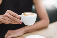 Close-up of senior woman holding a cup of cappuccino - DIGF05075