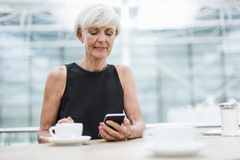 Senior woman using cell phone in a cafe - DIGF05078