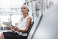 Senior woman sitting in waiting area with newspaper - DIGF05081