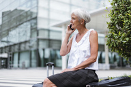 Smiling senior woman with baggage on cell phone in the city - DIGF05090