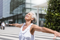 Happy senior woman with outstretched arms in the city - DIGF05093