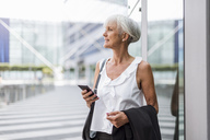 Senior woman with cell phone in the city looking around - DIGF05102