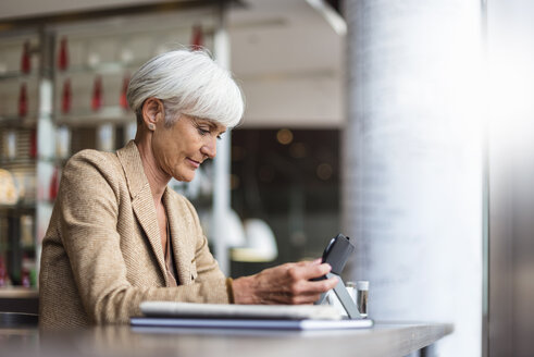 Senior businesswoman using tablet in a cafe - DIGF05105