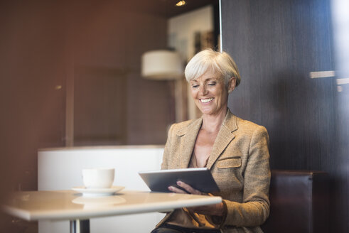 Smiling senior businesswoman using tablet in a cafe - DIGF05111