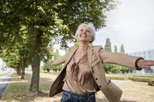 Happy senior woman with outstretched arms in a park - DIGF05114