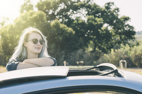Smiling woman in sunglasses standing by car against trees at farm during sunny day - TGBF00079