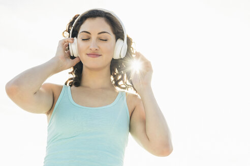 Smiling woman with closed eyes listening music through headphones against sky during sunny day - TGBF00100