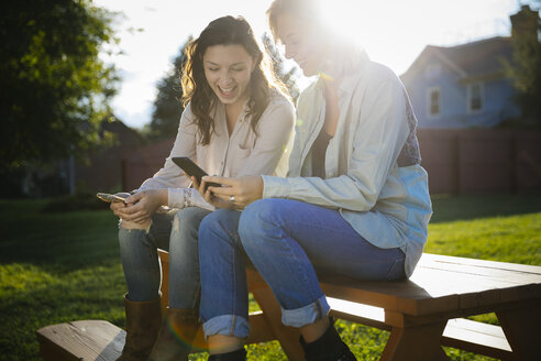Smiling young female friends using mobile phones while sitting on picnic table in lawn - TGBF00238