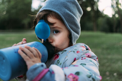 Portrait of fashionable little girl drinking water in a park - GEMF02409