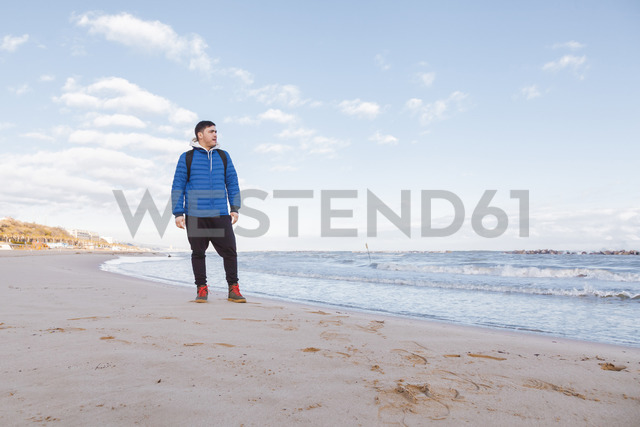 Italy, Molise, Termoli, young man standing at the beach, looking at distance - FLMF00020