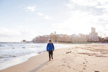 Italy, Molise, Termoli, young man walking at the beach - FLMF00023