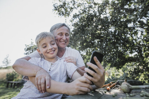 Happy grandmother and grandson taking a selfie in garden - KMKF00531