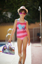 Young girl arriving at the pool in summer with bath clothes - JSMF00436