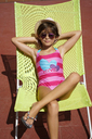 Young girl sitting in sun lounger, sunbathing - JSMF00442