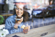 Smiling young woman speaking on phone in cafe while having tea - BSZF00568