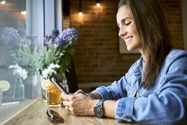 Smiling young woman using phone in cafe - BSZF00571