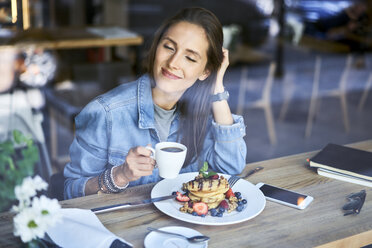 Smiling young woman enjoying pancakes and coffee in cafe - BSZF00580