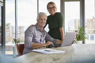 Portrait of smiling mature couple with laptop on table at home - RBF06502