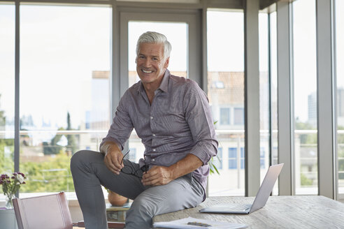 Portrait of smiling mature man with laptop sitting on table at home - RBF06505