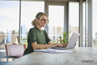 Smiling mature woman using laptop on table at home - RBF06508