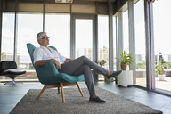 Mature man relaxing in armchair at the window at home - RBF06511