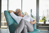 Portrait of smiling mature man relaxing in armchair at the window at home - RBF06517