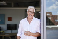 Portrait of smiling mature man holding coffee cup at the balcony at home - RBF06523