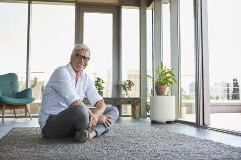 Smiling mature man relaxing sitting on carpet at home - RBF06526